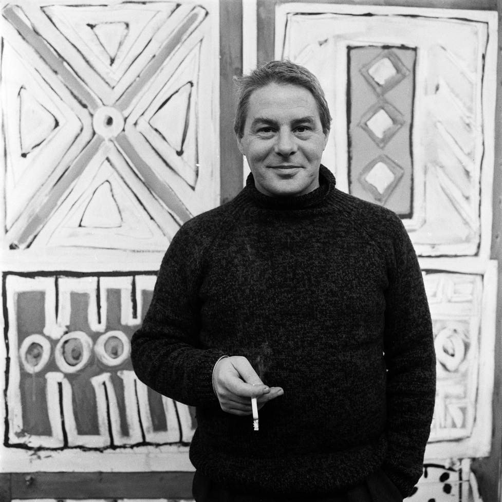 Lucebert in front of one of his works.